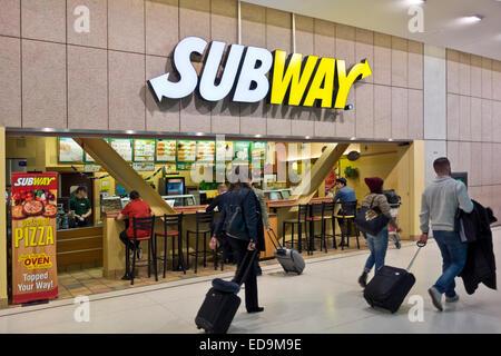 I viaggiatori di aria con le valigie passare da un sandwich di metropolitana ristorante all'Aeroporto di Toronto, Foto Stock
