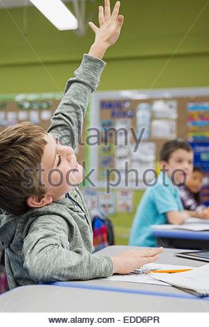Entusiasta studente elementare con la mano sollevata in aula Foto Stock