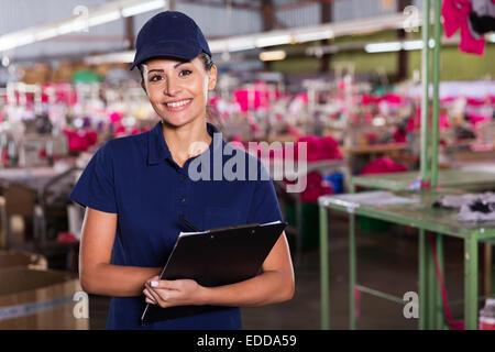 Allegro abbigliamento giovane supervisore di fabbrica in piedi nella zona di produzione Foto Stock