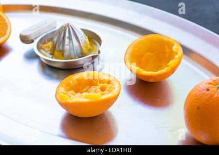 Spremuta di arance su un vassoio d'argento con argento metallico centrifuga a mano. Foto Stock