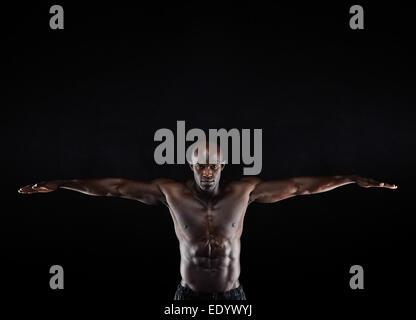 Ritratto di un forte giovane uomo muscolare stretching braccia contro uno sfondo scuro. Uomo di afro-americana in Foto Stock