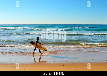 Unidentified surfer di camminare sulla spiaggia. Foto Stock