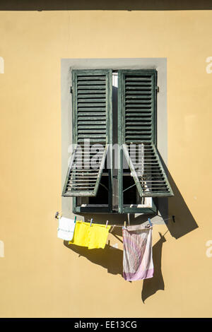 Finestra in una parete gialla con weathered persiane verdi e una linea di giallo rosa bianco asciugamani sotto l'asciugatura Foto Stock