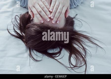 Donna sdraiata sul letto che copre la sua gli occhi con le mani Foto Stock