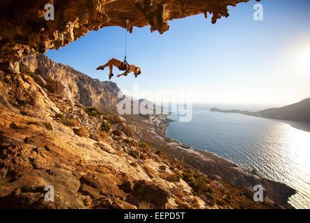 Female Rock scalatore appeso sulla corda dopo il fallito tentativo di prendere la prossima maniglia sulla scogliera Foto Stock