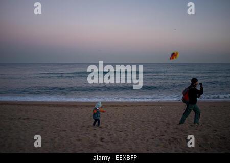 Barcellona, Spagna. Il 22 gennaio, 2015. Un uomo e un bambino tenta di volare un aquilone come il sole tramonta Foto Stock
