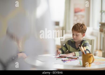 Ragazzo (6-7) seduto e disegno in camera per famiglia Foto Stock