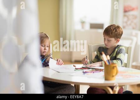 Sorella e fratello (4-5, 6-7) disegno nella family room Foto Stock