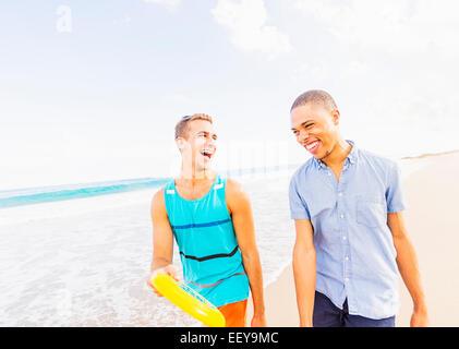 Stati Uniti d'America, Florida, Giove, giovane uomo a camminare e parlare, tenendo il disco di plastica sulla spiaggia Foto Stock
