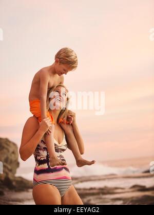 Stati Uniti, California, Laguna Beach, madre figlio portante (6-7) sulle spalle all'aperto Foto Stock