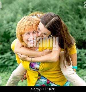 Madre dando sovrapponibile in sella alla sua figlia nel parco Foto Stock