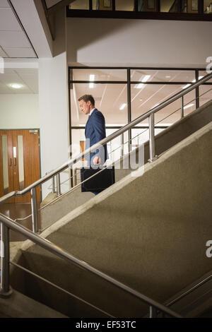 Imprenditore andando giù per le scale Foto Stock