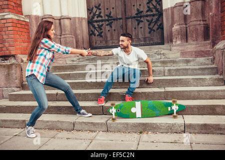 Coppia giovane con lo skateboard ingannare intorno a passi Foto Stock