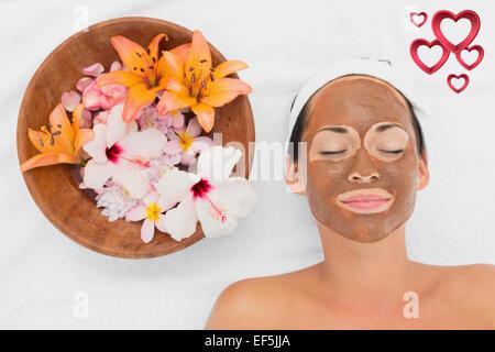 Immagine composita di sorridere brunette ottenendo un fango viso trattamento accanto al vaso di fiori Foto Stock