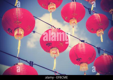 Retrò filtrato rosso cinese lanterne di carta contro il cielo blu. Foto Stock
