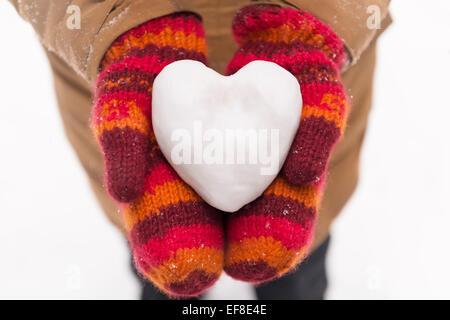 Woman in Red muffole tenendo un cuore fatto di neve, primo piano delle mani, concetto romantico Foto Stock