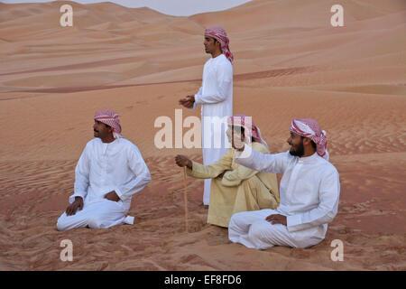 Gli uomini arabi in abito tradizionale in mezzo alle dune di sabbia di Liwa, Abu Dhabi, Emirati arabi uniti Foto Stock