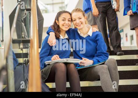 Ritratto di due allegro studentesse seduto sui gradini con bracci intorno Foto Stock