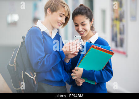 Due sorridenti studentesse indossano uniformi scolastiche guardando lo smartphone nel corridoio della scuola Foto Stock