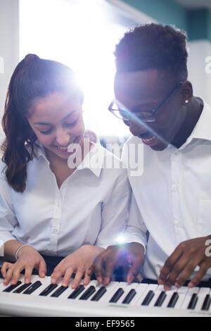 Allievi felici giocando sintetizzatore in aula Foto Stock