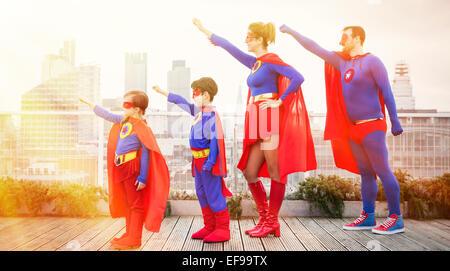 Famiglia di supereroi in piedi con le braccia distese sul tetto della città Foto Stock