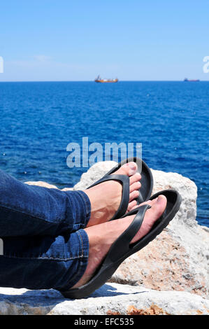 Primo piano dei piedi di un uomo con flip-flop che è rilassante vicino al mare in estate Foto Stock