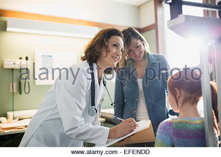 Pediatra controllo altezza della ragazza in sala esame Foto Stock