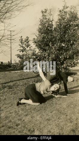 Il 12 Dic. 2014 - Canada - circa 1950: Riproduzione di un antico foto mostra due ragazze imbrogliamo intorno, posa sull'erba sullo sfondo del grande albero (credito Immagine: © Igor Golovniov/ZUMA filo/ZUMAPRESS.com) Foto Stock