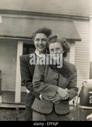 Il 12 Dic. 2014 - Canada - circa 1950: Riproduzione di un antico mostra fotografica di due donne in business tute in posa contro la casa privata nei pressi di un'auto di credito (Immagine: © Igor Golovniov/ZUMA filo/ZUMAPRESS.com) Foto Stock