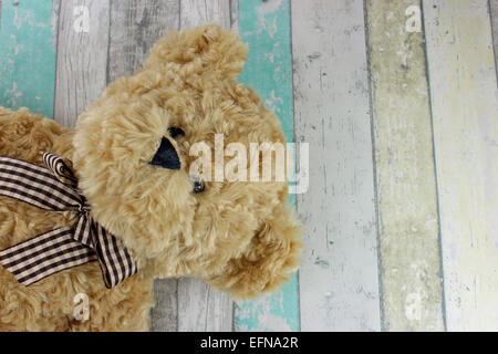 Simpatico orsacchiotto su un legno invecchiato sfondo. Foto Stock