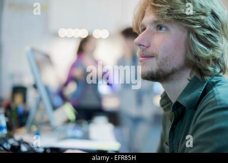 Un uomo che guarda verso l'alto dal suo compito in un computer repair shop. Foto Stock