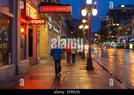 Persone il centro a piedi sulla notte piovosa-Victoria, British Columbia, Canada. Foto Stock