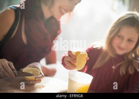 Una donna e una ragazza seduta al tavolo, ragazza spremendo il succo di un limone in un bicchiere. Foto Stock