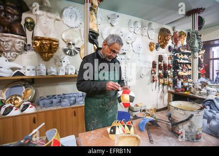 Un artigiano lavorando su una maschera in un carnevale maschere store di Venezia, Italia. Foto Stock