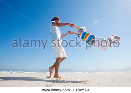 Sorridente padre figlio oscillanti intorno scherzosamente di sunny beach Foto Stock