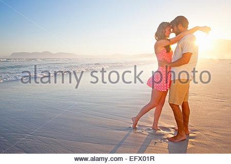 Coppia romantica che abbraccia circa al bacio di sunny beach Foto Stock