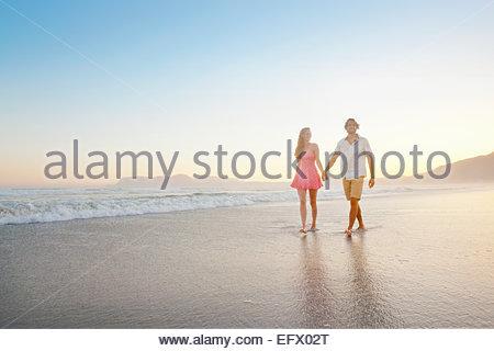 Giovane, tenendo le mani, passeggiate lungo la spiaggia Sunny Beach Foto Stock