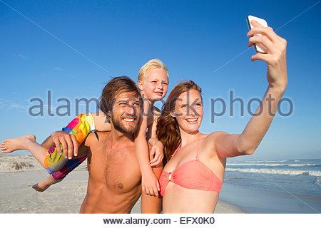 Ritratto di coppia felice con il figlio sulla spalla, tenendo selfie di sunny beach Foto Stock