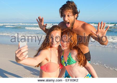 Ritratto di famiglia felice, tenendo selfie di sunny beach Foto Stock