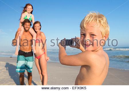 Ragazzo, sorridente alla fotocamera, prendendo foto di famiglia sulla spiaggia Sunny Beach Foto Stock