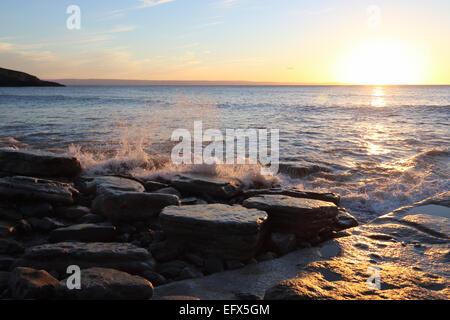 Onde che si infrangono sulle rocce sulla spiaggia di Gallese al crepuscolo Foto Stock