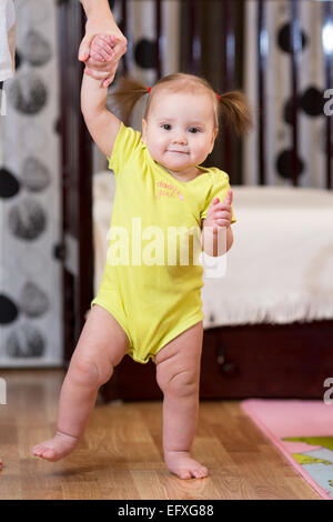 Baby prendendo i primi passi con la madre aiutare Foto Stock