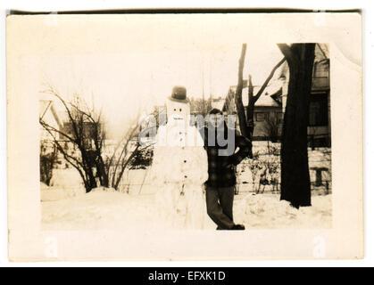 Il 12 Dic. 2014 - Canada - circa 1940s: Riproduzione di un antico mostra fotografica di uomo in posa accanto a un pupazzo di neve sullo sfondo della coperta di neve strade (credito Immagine: © Igor Golovniov/ZUMA filo/ZUMAPRESS.com) Foto Stock