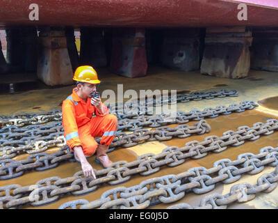 Lavoratori portuali in un cantiere navale a parlare su un walkie-talkie Foto Stock