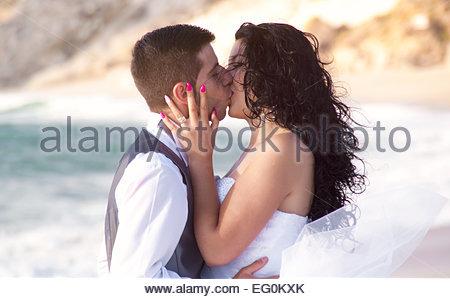 Lo sposo baciare la sua sposa sulla spiaggia Foto Stock