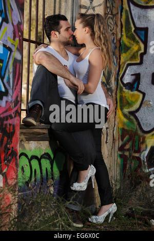 Coppia giovane kissing contro una finestra sbarrata in un edificio in rovina coperto di graffiti Foto Stock