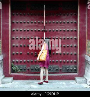 Donna spiata attraverso la porta, la Città Proibita di Pechino, Cina Foto Stock