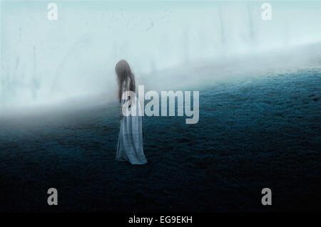 Donna che cammina sulla collina misty Foto Stock