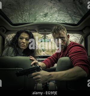 L uomo e la donna in auto con pistola Foto Stock