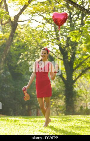 Donna con cuore rosso forma palloncino passeggiate nel parco Foto Stock